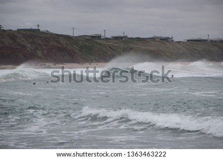 Windy spray from surf cliff background surfers foreground #1363463222