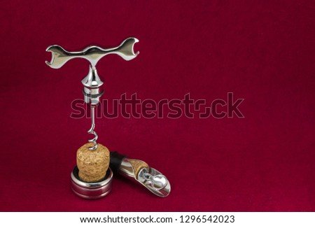 wine accessories corkscrew funnel ring and cork on a red background