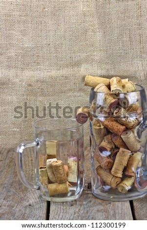 Wine against beer. Two beer mugs filled with corks from wine bottles are on the rough wooden table. Sackcloth background.