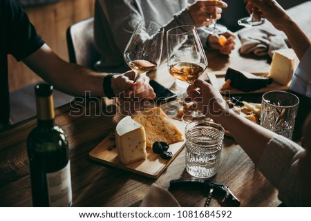Wine and cheese served for a friendly party in a bar or a restaurant. - Shutterstock ID 1081684592