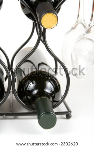 wine and glasses on a rack on a white background - stock photo