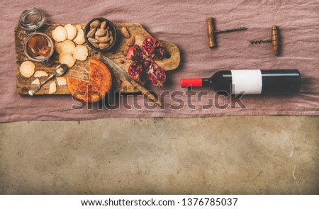 Wine and snack set. Flat-lay of wine bottle with blank label, vintage corkscrews and cheese and appetizers board over dusty pink linen table cloth, top view, copy space. Party food concept #1376785037