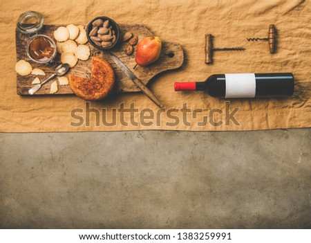 Wine and snack set. Flat-lay of wine bottle with blank label, vintage corkscrews and cheese and appetizers board over dusty yellow linen tablecloth, top view, copy space. Party food concept #1383259991