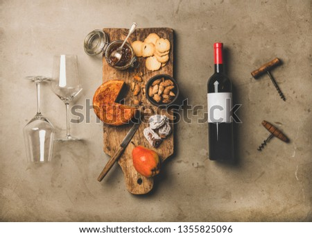 Wine and snack set. Flat-lay of wine bottle with blank label, vintage corkscrews, two wineglasses and cheese and appetizers board over concrete background, top view. Party food concept #1355825096