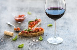 Wine appetizer set. Glass of red wine, brushettas with fresh tomato and basil on over rustic grunge grey backdrop