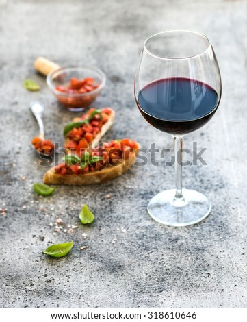 Wine appetizer set. Glass of red wine, brushettas with fresh tomato and basil on over rustic grunge grey backdrop #318610646