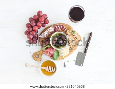 Wine appetizer set. Glass of red wine, grapes, honey, parmesan cheese, meat variety, bread slices, pecan nuts, honey, olives and basil on rustic wooden board over white wood backdrop, top view