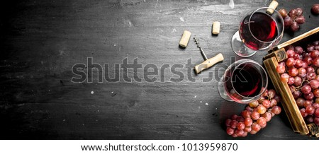 Wine background. Red wine in an old box with a corkscrew. On the black chalkboard.