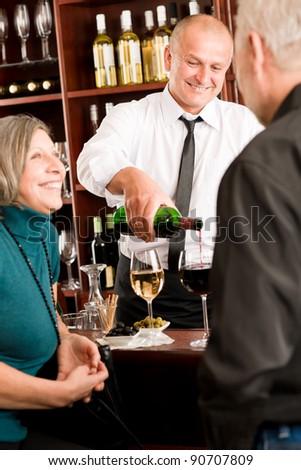 Wine bar happy senior people having drink smiling barman