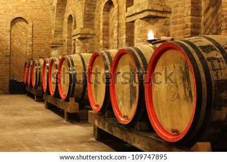 Wine barrels and bottles in a vineyard cellar with a lighting candle. The picture was taken in Csopak, Balaton, Hungary