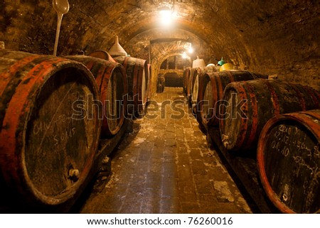 Wine barrels and bottles in the back in a cellar . Warm colors, wide angle view.
