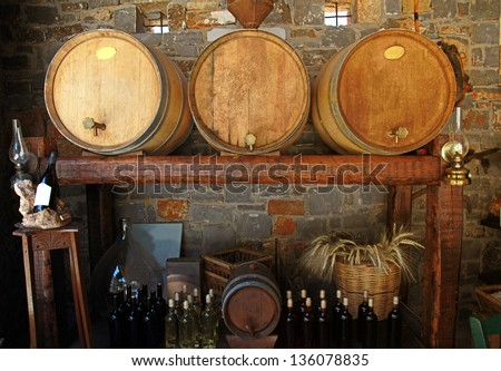 Wine barrels and bottles in the old cellar of a winery.
