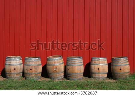 Wine barrels at a vineyard against a red barn wall, rural scene