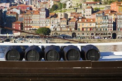 Wine barrels in Porto. Five barrels of Port wine on a boat. The town of Porto as a background.