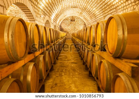 Wine barrels stacked in the cellar of the winery #1010856793