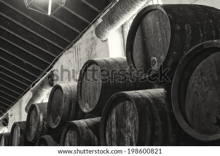 Wine barrels stacked in winery old, in black and white