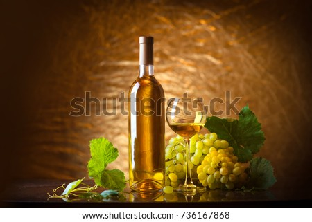 Wine. Bottle and a glass of white wine with ripe grapes still life. White wine on a black background. The boundaries of art design #736167868