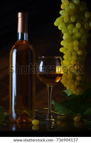 Wine. Bottle and a glass of white wine with ripe grapes still life. White wine on a black background. The boundaries of art design #736904137