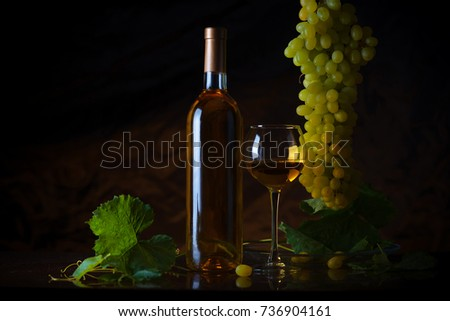 Wine. Bottle and a glass of white wine with ripe grapes still life. White wine on a black background. The boundaries of art design #736904161