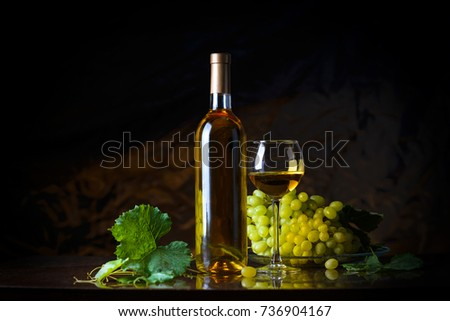 Wine. Bottle and a glass of white wine with ripe grapes still life. White wine on a black background. The boundaries of art design #736904167