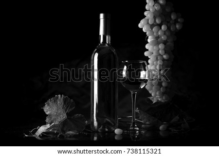 Wine. Bottle and a glass of white wine with ripe grapes still life. White wine on a black background. The boundaries of art design #738115321