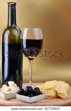 wine bottle and cheese on gold background