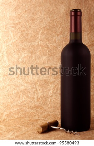 wine bottle and corkscrew on a paper background
