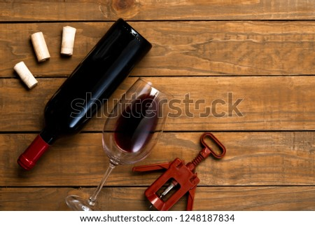 Wine bottle and glass corkscrew and corkscrew on wooden background. Top view with copy space. #1248187834