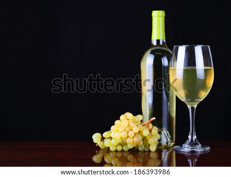 Wine Bottle and Glass of White Wine with Fresh Grapes over black background.