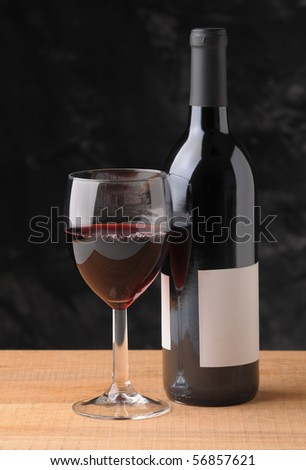 Wine Bottle and Glass on Wood Table with dark background. Vertical format