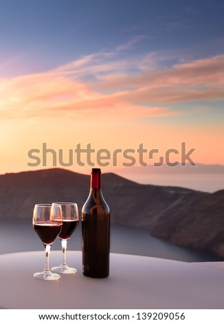 Wine bottle and glasses overlooking Santorini cliffs