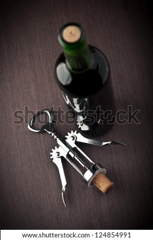 wine bottle and metal corkscrew