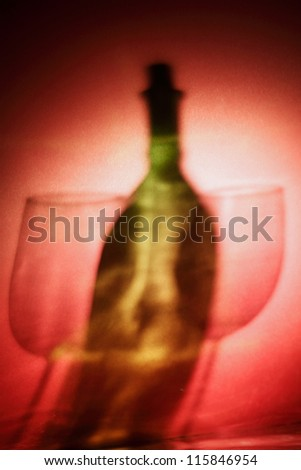 Wine bottle and wine glasses on red background