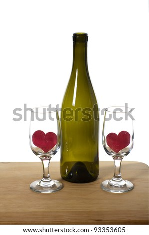 Wine bottle and wine glasses with hearts sitting on table