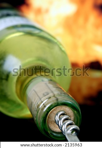 Wine bottle by orange flames with silver corkscrew, macro, close up