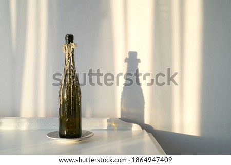 wine bottle candlestick with melted paraffin on a vintage white cabinet and a beautiful sun reflection on the wall - an interior design and style concept Foto stock ©