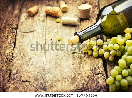 Wine bottle , grape and corks on wooden table / summer wine background