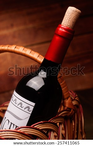 Wine bottle in a basket on wooden table, label is self made