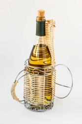 Wine bottle in a whicker wine holder on white surface