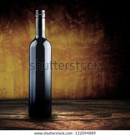 Wine bottle on wood floor and grunge background - stock photo
