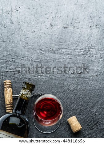 Wine bottle, wine glass and corkscrew on the graphite board. #448118656