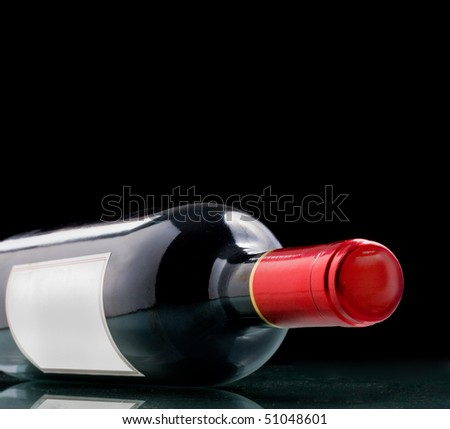 Wine bottle with blank paper generic tag on black background
