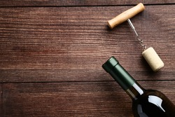 Wine bottle with cork and corkscrew on brown wooden table