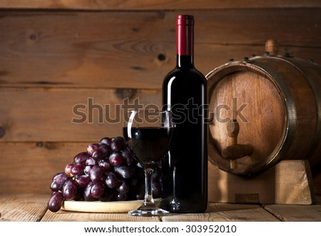 Wine bottle with glass, bunch of grapes and wooden barrel on old wooden background