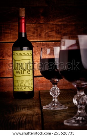 Wine bottle with self made label  and glasses filled with wine on wooden table