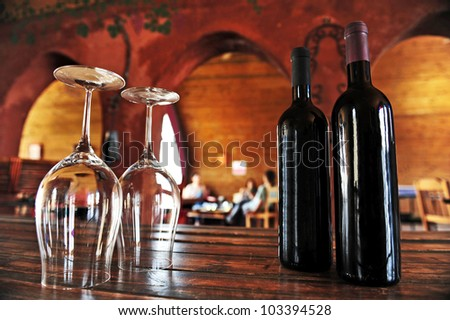 Wine bottles and wine glasses in a vineyard.