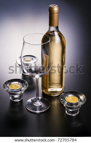 Wine bottles, glasses and candles beside.
