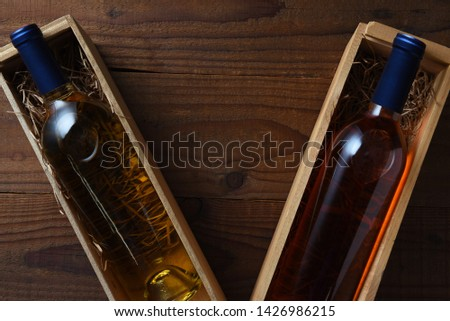 Wine bottles in wood boxes on a rustic wooden table. The individual boxes of white wine and blush are at an angle with copy space between.  #1426986215