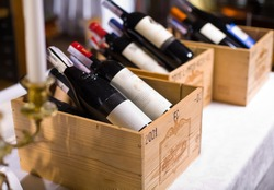 Wine bottles in wooden boxes are on the table restaurant. Wine background.
