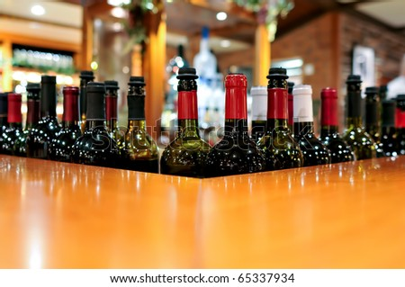 wine bottles lined beside lovely bar with copy space, focus on nearest bottle